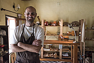 Portrait of smiling luthier in his workshop - ABZF000794