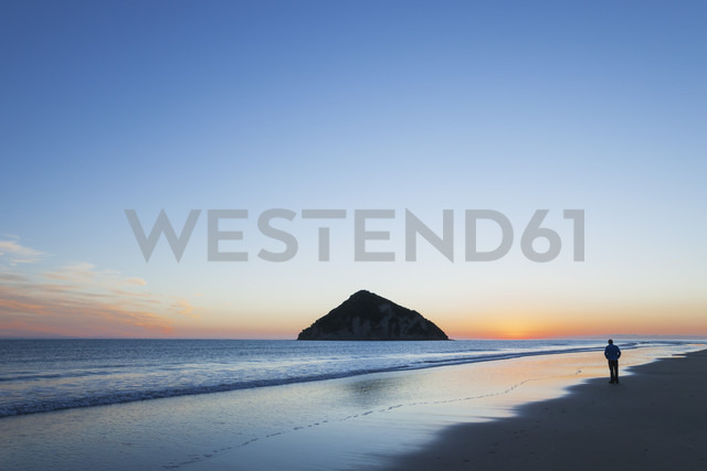 New Zealand, East Cape, Anaura Bay before sunrise, man watching the first sunlight - GWF004778 - Gaby Wojciech/Westend61