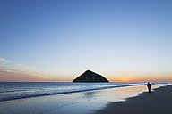New Zealand, East Cape, Anaura Bay before sunrise, man watching the first sunlight - GWF004778