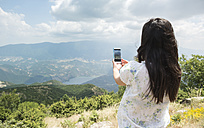 Greece, Central Macedonia, woman taking smartphone picture in the mountains - DEGF000871