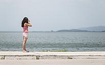 Greece, Amfilochia, woman taking picture at the sea - DEGF000874