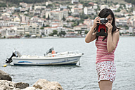 Greece, Amfilochia, woman taking picture at the sea with vintage camera - DEGF000877