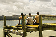 Back view of three friends sitting on a jetty - UUF007928