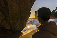 New Zealand, Wanganui, back view of man on the beach watching sunrise - UUF007940