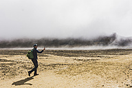 New Zealand, Tongariro National Park, hiker taking a photo with smartphone - UUF007946