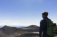 New Zealand, Tongariro National Park, hiker looking at view - UUF007949