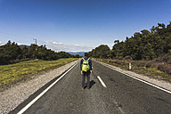 New Zealand, Tongariro National Park, back view of hiker with backpack standing on country road - UUF007952