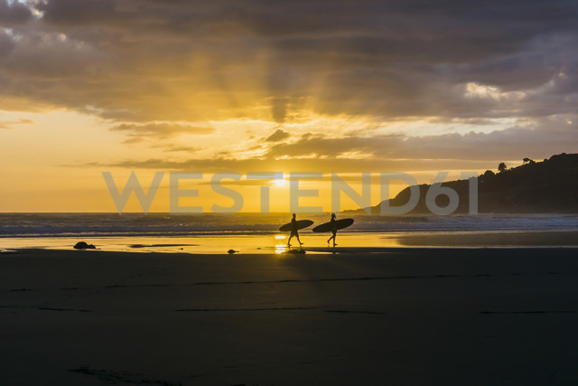 Silhouettes of two people with surfboards on the beach at twilight - UUF007958 - Uwe Umstätter/Westend61