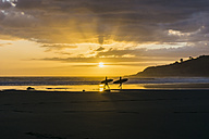 Silhouettes of two people with surfboards on the beach at twilight - UUF007958