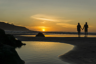 Silhouette of couple standing hand in hand on the beach looking at sunset - UUF007964
