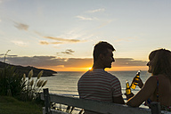 Couple sitting on bench at sunset toasting with beverages in glass bottles - UUF007967