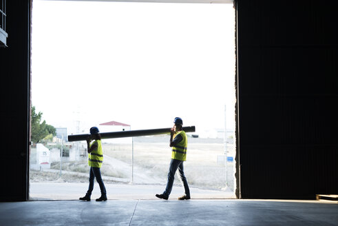 Construction workers carrying pipe in warehouse - JASF000940