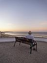 Portugal, Senior man siting on bench watching sunrise - LAF001658
