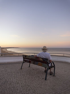 Portugal, Senior man siting on bench watching sunrise - LAF001658