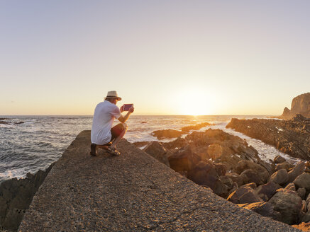 Portugal, Senior man sitting on wall at harbour at sunset, taking picture with digital tablet - LAF001664