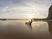 Portugal, Senior man sitting at beach, reading book - LAF001673