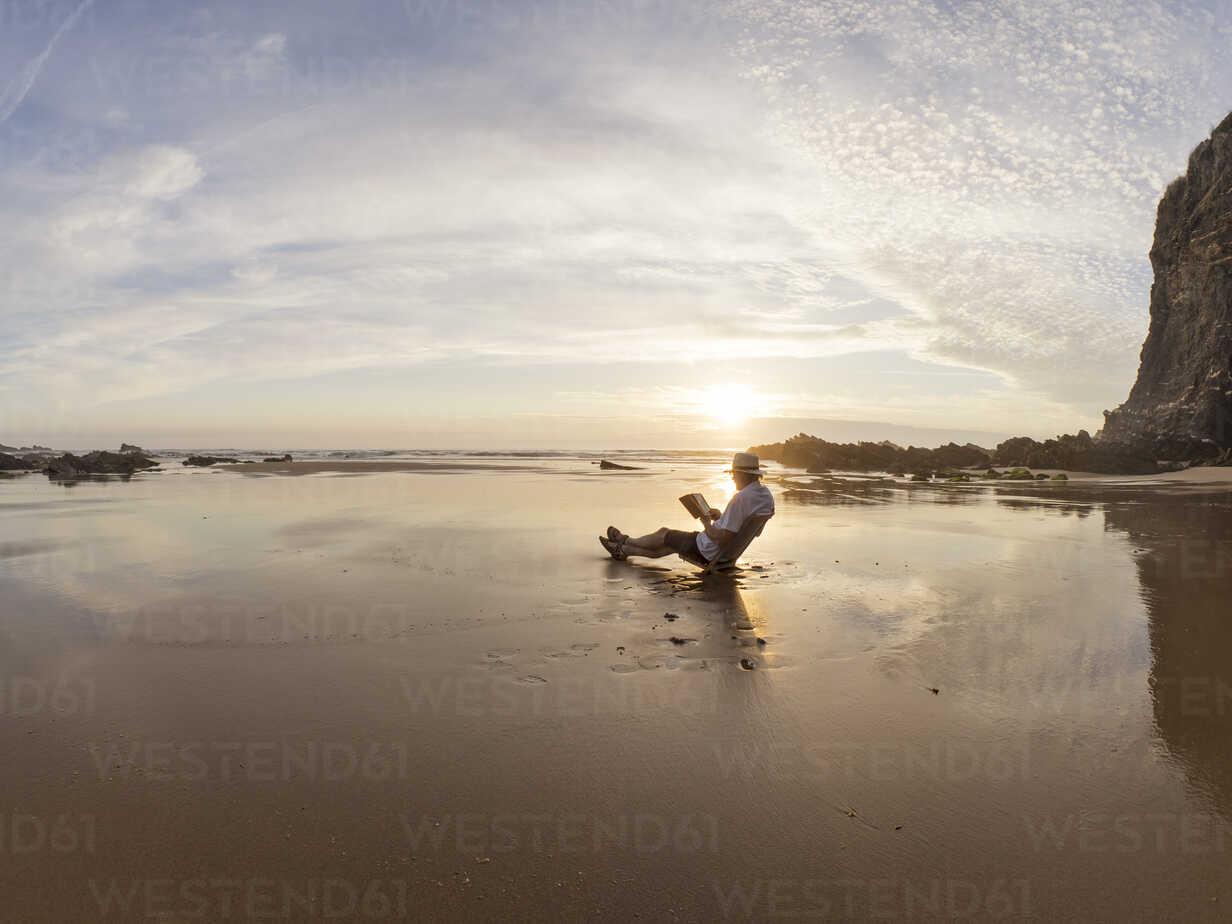 Portugal, Senior man sitting at beach, reading book - LAF001673 - Albrecht Weißer/Westend61