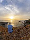 Portugal, Senior man sitting at bay watching sunset - LAF001679