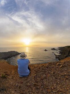 Portugal, Senior man sitting at bay watching sunset - LAF001679