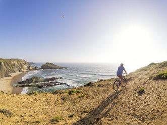 Portugal, Senior man mountain biking at the sea - LAF001694