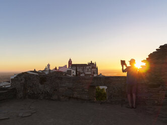 Portugal, Senior man photographing sunrise at Castel de Monsaraz - LAF001697