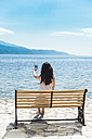 Greece, Sergoulas, woman sitting on bench at the coast taking pictures with smartphone - DEGF000900