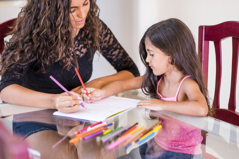 Teenage girl drawing with her little sister at table - SIPF000615