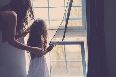 Teenage girl and her little sister looking through window - SIPF000636