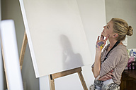 Woman observing canvas before setting up artwork at home studio - ZEF008879