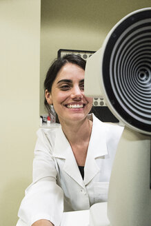 Ophthalmologist smiling, examining eyesight in an ophthalmic clinic - ABZF000799