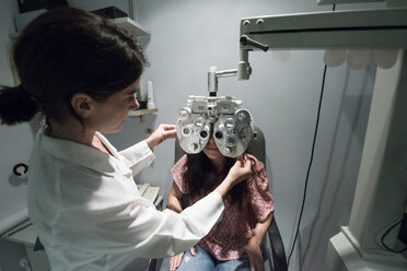 Ophthalmologist adjusting an optometrist phoropter, for eye calibration of a patient - ABZF000802