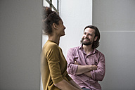 Young couple sitting in flat and talking to each other - RBF004608