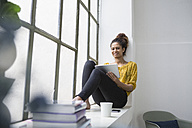Woman sitting on window sill using digital tablet - RBF004644