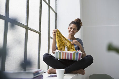 Young woman sitting on window sill unpacking parcel - RBF004647