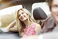 Portrait of smiling blond woman sitting on passenger seat in a car - PESF000188