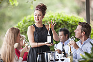 Waitress showing wine bottle to clients in restaurant - ZEF008899