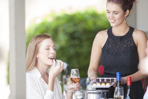 Woman enjoying wine and chocolates served in restaurant - ZEF008917