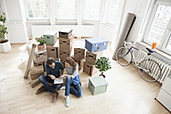 Couple surrounded by cardboard boxes with plan on floor - RBF004678