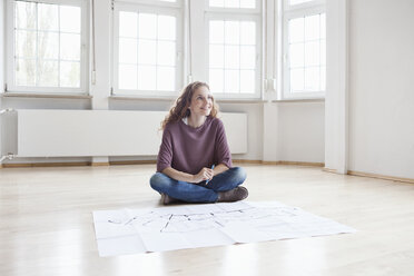 Smiling woman with construction plan in empty apartment - RBF004681