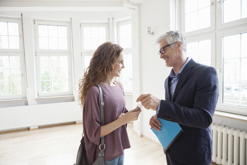 Real estate agent handing over key to client - RBF004684