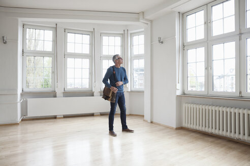 Man looking around in empty apartment - RBF004687
