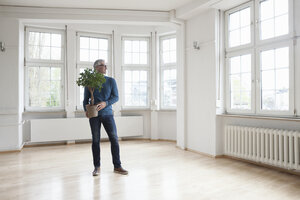Man holding plant in empty apartment - RBF004690
