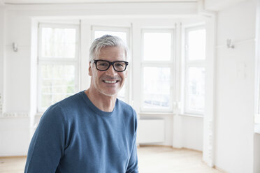 Portrait of smiling man in empty apartment - RBF004696