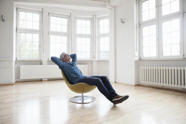 Relaxed man sitting in armchair in empty apartment - RBF004699