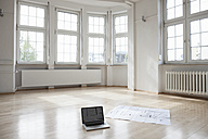 Laptop and construction plan on floor in empty apartment - RBF004705