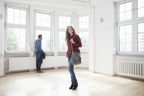 Couple looking around in empty apartment - RBF004714