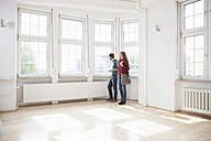 Couple looking around in empty apartment - RBF004717