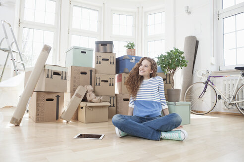 Woman surrounded by cardboard boxes sitting on floor - RBF004723