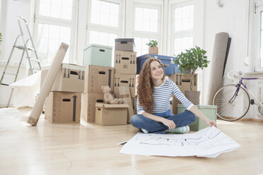 Woman surrounded by cardboard boxes sitting on floor with construction plan - RBF004726