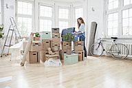 Woman in new apartment unpacking cardboard box - RBF004729